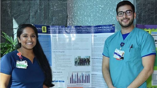 two nurses giving a poster presentation